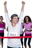 Szczęśliwy zwycięzca atlety mety z rękami podnosić skrzyżowanie Fotografia Stock