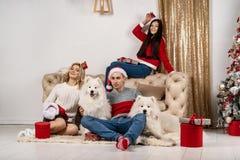 Szczęśliwych Świąt Bożego Narodzenia świętować młodzi ludzie z psami i prezentami obraz royalty free
