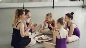Szczęśliwych dzieci baletniczy ucznie i ich nauczyciel jedzą pizzę podczas przerwa na lunch między dancingowymi lekcjami Dziewczy zbiory