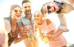 Szczęśliwych millennial przyjaciół grupowy bierze selfie przy zabawy plaży przyjęciem zdjęcia royalty free