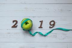 2019 Szczęśliwych nowy rok dla opieki zdrowotnej, Wellness i medycznego pojęcia, zielony jabłko, pomiarowa taśma i drewniana licz zdjęcia stock