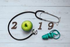 2019 Szczęśliwych nowy rok dla opieki zdrowotnej, Wellness i medycznego pojęcia, zielony jabłko, pomiarowa taśma i drewniana licz zdjęcie stock