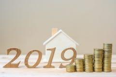 2019 Szczęśliwych nowy rok z złocistych monet stertą i drewnianej liczba na stole biznes, inwestycja, emerytury planowanie, finan zdjęcie stock