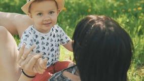 Szczęśliwych potomstw macierzysty bawić się na koc z jej ślicznym synem pod drzewem przy parkiem zdjęcie wideo