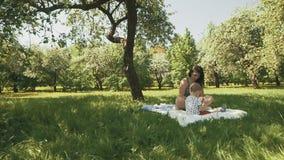 Szczęśliwych potomstw macierzysty bawić się na koc z jej małym synem pod drzewem przy parkiem zbiory
