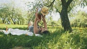 Szczęśliwych potomstw macierzysty bawić się na koc z jej synem pod drzewem przy parkiem zbiory wideo