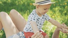Szczęśliwych potomstw macierzysty bawić się na koc z jej uroczym synem pod drzewem przy parkiem zdjęcie wideo