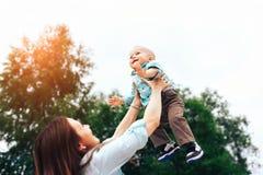 Szczęśliwych potomstw macierzysty bawić się z jej małym synem plenerowym obraz stock