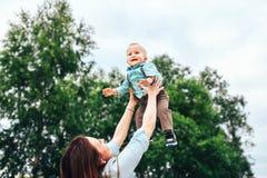 Szczęśliwych potomstw macierzysty bawić się z jej małym synem plenerowym zdjęcia stock