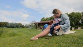 Szczęśliwych potomstw macierzysty cuddling przy parkiem i bawić się z jej małym dziecko synem na trawie zdjęcie wideo