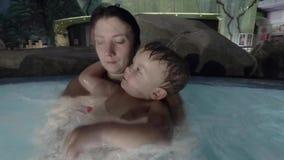 Szczęśliwych potomstw mienia dziecka macierzysty syn na rękach ono uśmiecha się i bawić się z on w basenie, zbiory