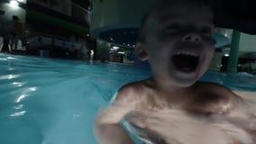 Szczęśliwych potomstw mienia dziecka macierzysty syn na rękach ono uśmiecha się i bawić się z on w basenie, zbiory wideo