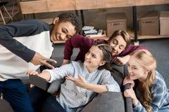 Szczęśliwych wielokulturowych nastolatków grupowy bierze selfie na smartphone i obsiadanie na kanapie w domu obrazy stock