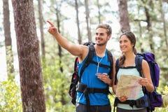Szczęśliwych wycieczkowiczy mienia przyglądająca oddalona mapa i kompas Fotografia Stock