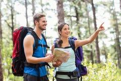 Szczęśliwych wycieczkowiczy mienia przyglądająca oddalona mapa i kompas Zdjęcia Stock