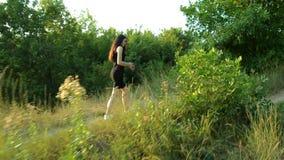 Szczęsliwa młoda brunetka w czerni sukni iść na zieleni polu wśród drzew i trawy zbiory wideo