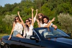 Szczęsliwe eleganckie młode ciemnowłose dziewczyny i faceci w okularach przeciwsłonecznych uśmiechają się w czarnym kabriolecie n obrazy stock