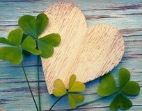 Szczęsliwe koniczyny z starym drewnianym sercem na błękita rocznika drewna b Fotografia Stock