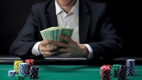 Szczęsliwy kasynowy zwycięzca trzyma dolarowych banknoty, układy scaleni na stole wokoło, gemowa nagroda obrazy royalty free