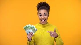Szcz??liwa czarna kobieta wskazuje przy euro banknotami w r?ce, pieni??ny sukces, pensja obraz stock