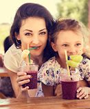 Szcz??liwa dzieciak dziewczyna i ?mieszna emocjonalna matka pije jagody smoothie sok w ulicznej kawiarni wp?lnie zbli?enie obraz stock