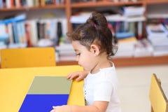Szcz??liwa dziecko ma?a dziewczynka czyta ksi??k? fotografia royalty free