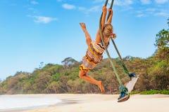 Szczęśliwa dziewczyna zabawy kołyszącą wysokość w w połowie powietrzu zdjęcie stock