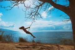 Szczęśliwa dziewczyna zabawy kołyszącą wysokość w w połowie powietrzu zdjęcia stock