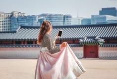 Szcz??liwa Europejska turystyczna kobieta w krajowym Korea?skim kostiumu chodzi przez pa?ac z telefonem zdjęcie stock