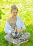 Szcz??liwa kobieta medytuje siedzie? w Lotosowej pozie na trawie Pi?kna boho stylu kobieta z akcesoriami cieszy si? s?onecznego d obraz royalty free
