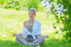 Szcz??liwa kobieta medytuje siedzie? w Lotosowej pozie na trawie Pi?kna boho stylu kobieta z akcesoriami cieszy si? s?onecznego d fotografia stock