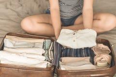 Szcz??liwa kobieta planuje podr?? przygotowywa walizk? obrazy royalty free