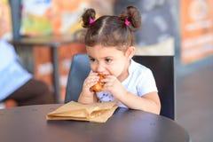 Szcz??liwa ?liczna dziewczyna na cukiernianego ?asowania ?wie?ym croissant na ciep?ym dniu, fotografia royalty free