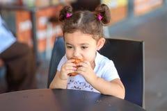 Szcz??liwa ?liczna dziewczyna na cukiernianego ?asowania ?wie?ym croissant na ciep?ym dniu, obraz stock