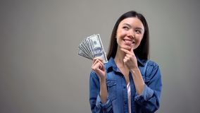 Szcz??liwa m?oda dama trzyma dolarowych banknoty, my?le? o zakupy lub wakacje obraz royalty free