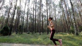 Szcz??liwa m?oda kobieta jogging w lesie w?r?d drzew Tropi? strza? z stabilizowan? kamer? zbiory