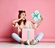 Szcz??liwa m?oda kobieta z prezentami nad r??owym t?em zdjęcia royalty free