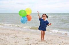 Szcz??liwa ma?a dziewczynka bawi? si? kolorowych balony na pla?y podczas wakacje fotografia royalty free