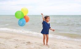 Szcz??liwa ma?a dziewczynka bawi? si? kolorowych balony na pla?y podczas wakacje obraz stock