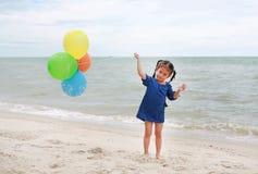 Szcz??liwa ma?a dziewczynka bawi? si? kolorowych balony na pla?y podczas wakacje obrazy stock