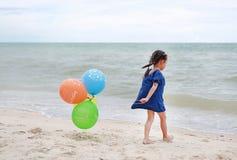 Szcz??liwa ma?a dziewczynka bawi? si? kolorowych balony na pla?y podczas wakacje obraz royalty free