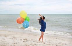 Szcz??liwa ma?a dziewczynka bawi? si? kolorowych balony na pla?y podczas wakacje fotografia stock