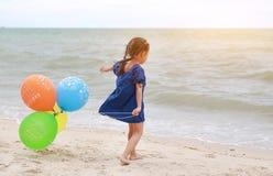 Szcz??liwa ma?a dziewczynka bawi? si? kolorowych balony na pla?y podczas wakacje zdjęcie royalty free