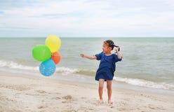 Szcz??liwa ma?a dziewczynka bawi? si? kolorowych balony na pla?y podczas wakacje zdjęcia royalty free