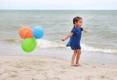 Szcz??liwa ma?a dziewczynka bawi? si? kolorowych balony na pla?y podczas wakacje obrazy royalty free
