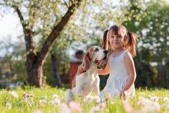 Szcz??liwa ma?a dziewczynka bawi? si? z psem w ogr?dzie zdjęcia stock