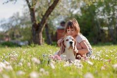 Szcz??liwa ma?a dziewczynka bawi? si? z psem w ogr?dzie zdjęcie stock