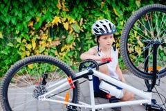 Szcz??liwa ma?e dziecko ch?opiec naprawia jego bicykl w bia?ym he?mie obrazy royalty free