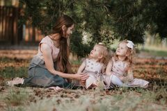 Szcz??liwa rodzina - mama i dwa c?rki siedzimy w czytaniu i ??ce ksi??ka piknik zdjęcie stock