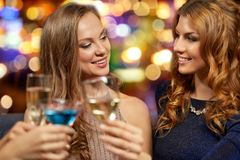 Szcz??liwe kobiety clinking szk?a przy noc klubem obraz stock
